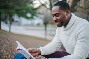 guy-outside-reading-book-sweater